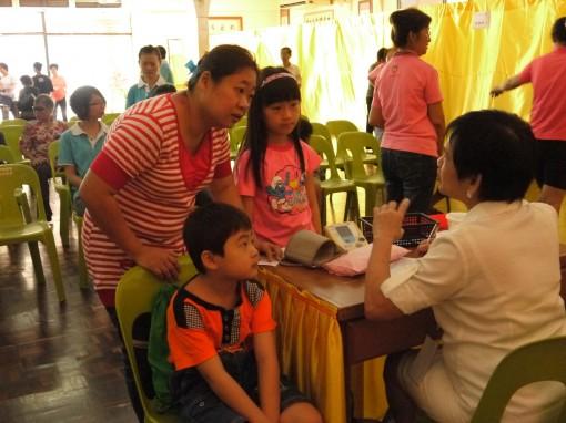 朱月娇医师为小朋友看诊时,家长在一旁询问情况。
