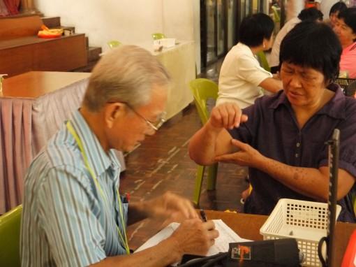 蔡启和医师为病黎看诊。